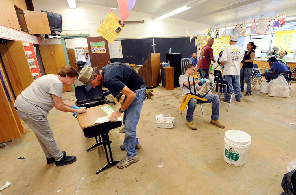 . Jerri Murtishaw, and Keith Gibson, both left, clean desks in a classroom at Crest View Elementary on Tuesday. Workers from Servpro and other disaster clean up contractors work on flood Damage at Crest View Elementary in Boulder on September 17, 2013. For more flooding videos and photos, www.dailycamera.com. Cliff Grassmick  / September 17, 2013