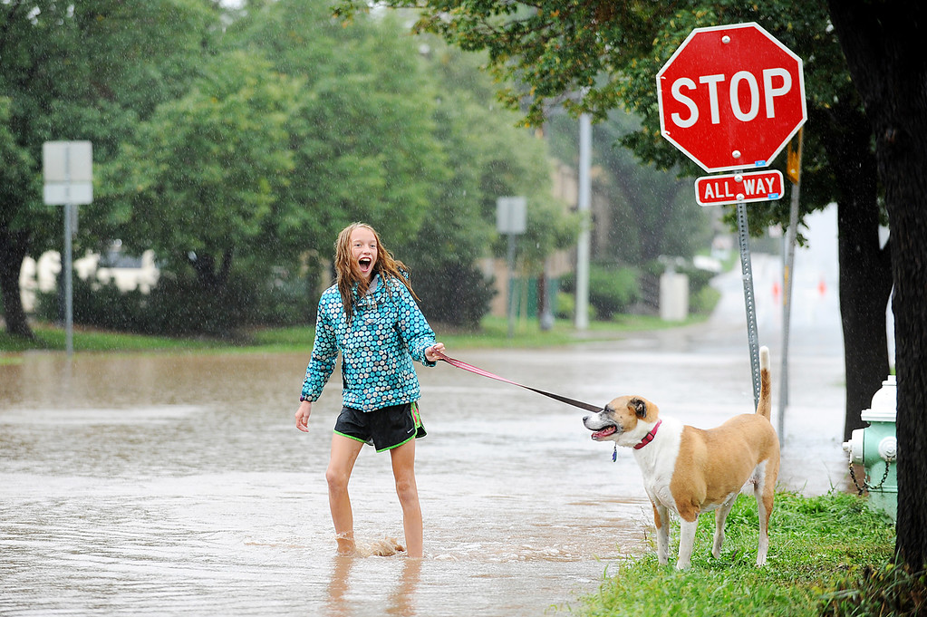 . Boulder\'s Georgia Weeks, 11, plays with her dog Lulu in the flood waters at the corner of Balsam and 9th Street in Boulder on Thursday, September 12, 2013. (Kira Horvath/ Daily Camera)