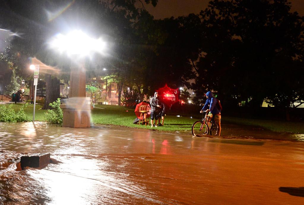 . A cyclist is seen across a flooded sidewalk, Thursday, Sept. 12, 2013, in Boulder. (Matthew Jonas/Times-Call)