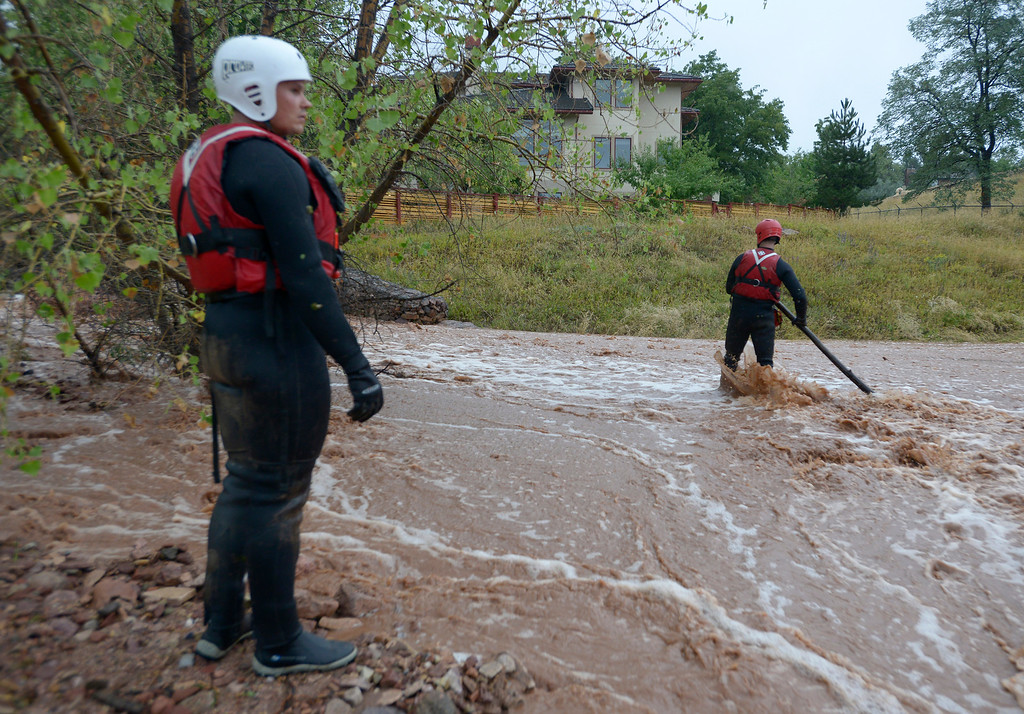 . Brighton Fire Rescue firefighters Brian Guyer, at left, and Clint Mader search for a possible drowning victim during the heavy flooding on Thursday in Boulder. For a video of the flooding go to www.dailycamera.com  Jeremy Papasso/ Camera
