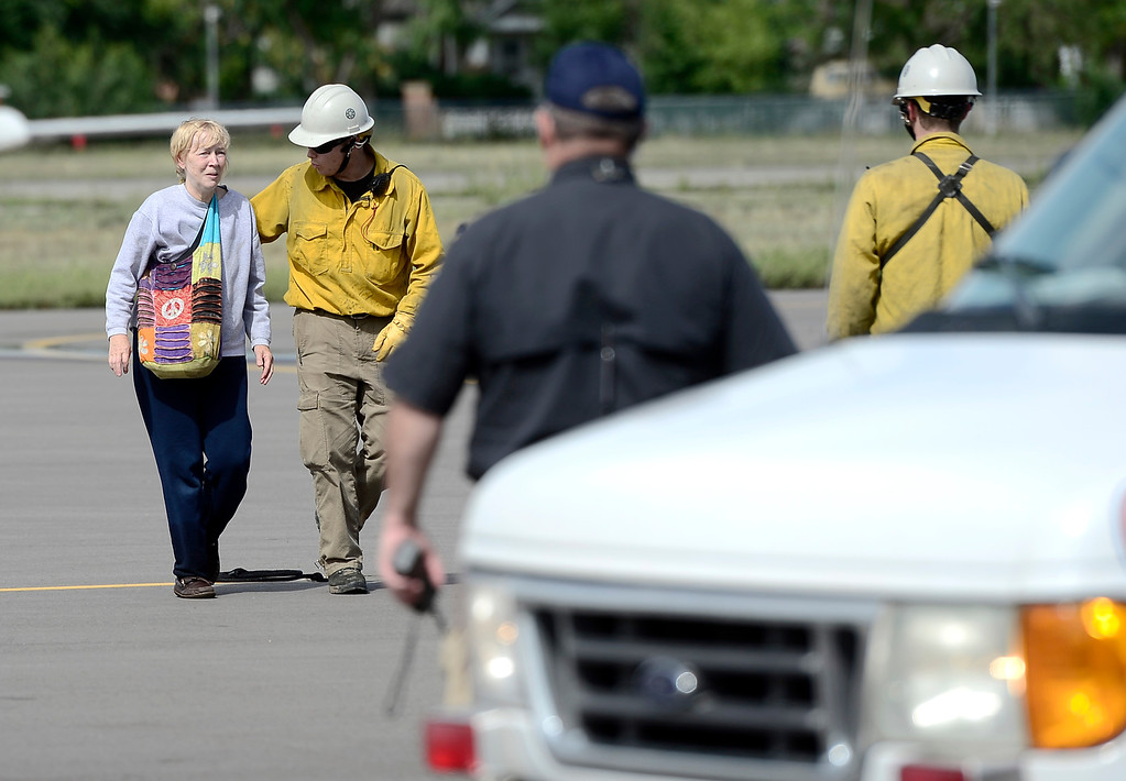 . A woman is directed off the tarmac at Boulder Municipal Airport after being flown down from Jamestown on a National Guard helicopter after being stranded from heavy rains in Boulder, Colorado September 13, 2013. BOULDER DAILY CAMERA/ Mark Leffingwell