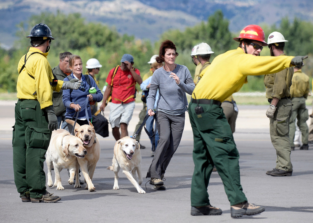 . Evacuees are directed to the airplane hangar after being rescued by helicopter from Pinewood Springs on Monday, Sept. 16, at the Boulder Municipal Airport in Boulder. For more photos and video of the flood rescue go to www.dailycamera.com Jeremy Papasso/ Camera