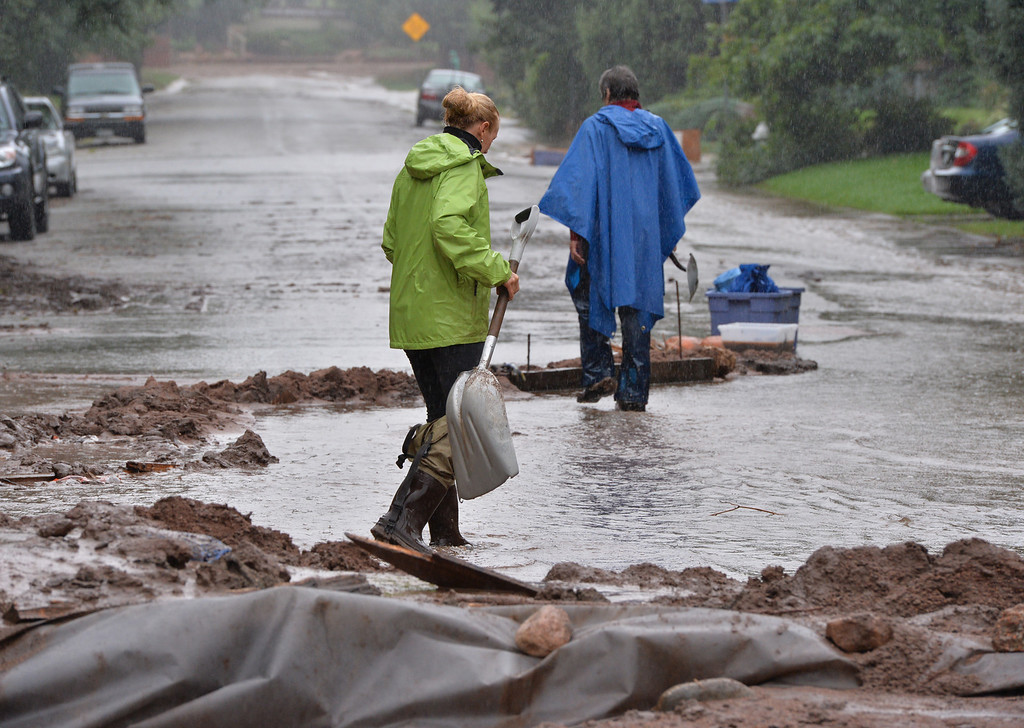 . People work on damming water flowing  along Mariposa Ave. and 20th St. in Boulder on Thursday. September 12, 2013 staff photo/ David R. Jennings