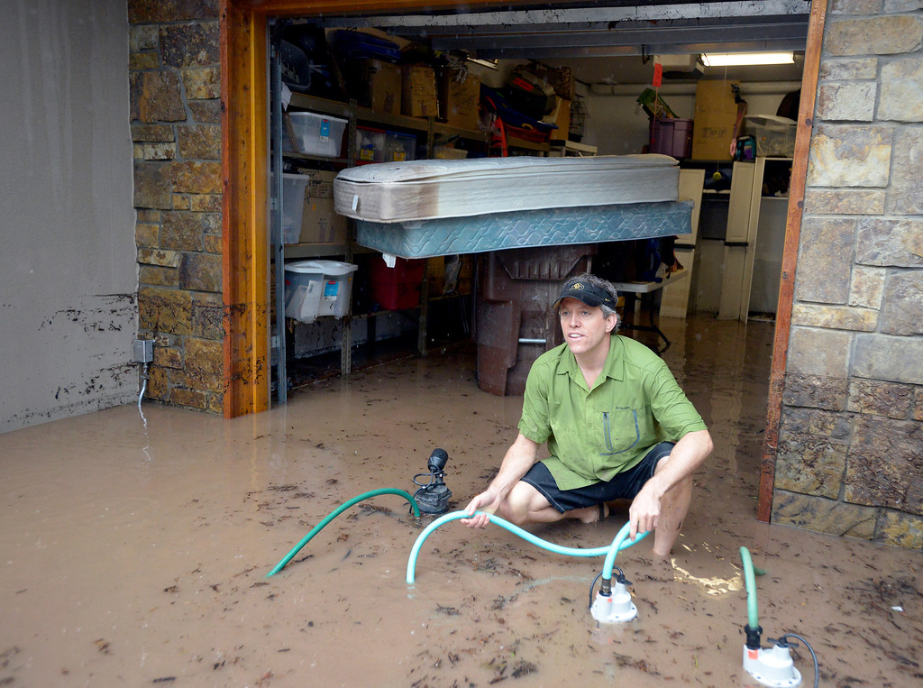 . Homeowner Chris Drummond works to remove water from his flooded basement during the heavy flooding on Thursday in Boulder. For a video of the flooding go to www.dailycamera.com  Jeremy Papasso/ Camera