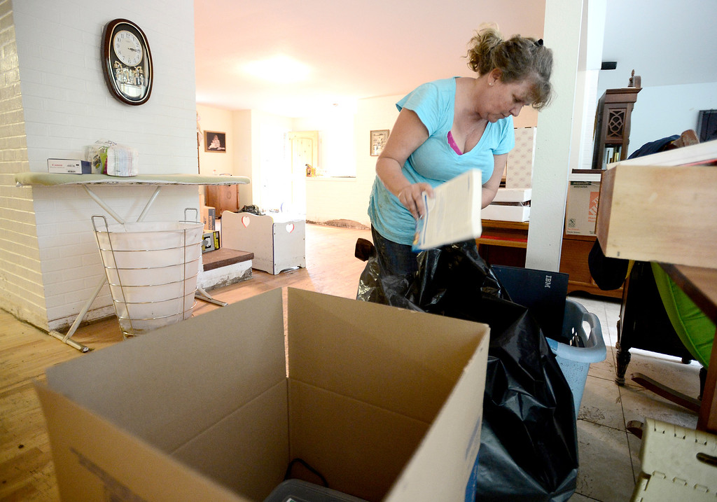 . Mary Bogetveit bags wet books to trash after water filled her home on Gapter Road from heavy rains causing flooding in Boulder, Colorado September 14, 2013. BOULDER DAILY CAMERA/ Mark Leffingwell