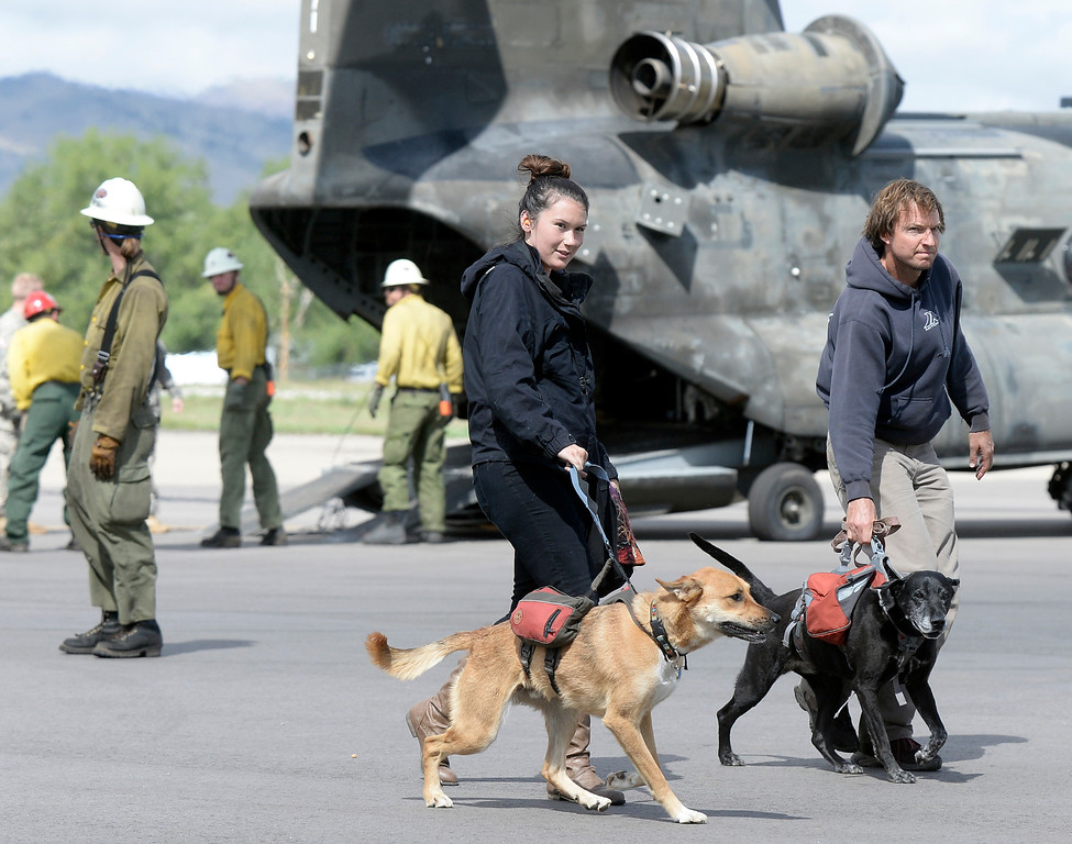. Evacuees walk their dogs off the tarmac after being rescued by helicopter from the Pinewood Springs area on Monday, Sept. 16, at the Boulder Municipal Airport in Boulder. For more photos and video of the flood rescue go to www.dailycamera.com Jeremy Papasso/ Camera