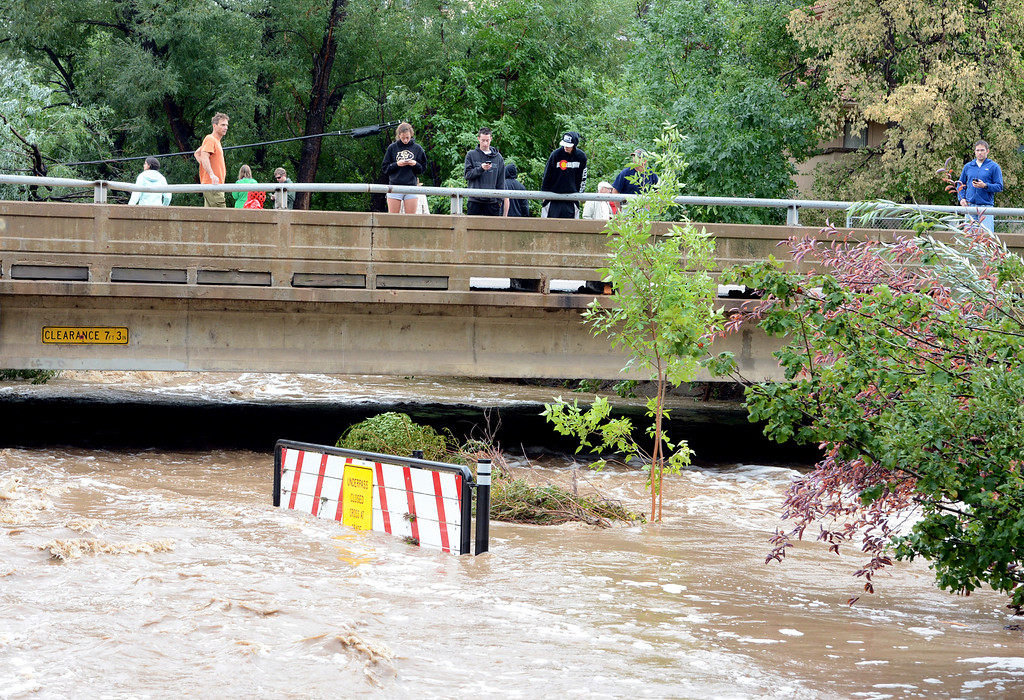 . People watch the flood waters in Boulder Creek at the Folsom Street bridge. For more flooding videos and photos, www.dailycamera.com. Cliff Grassmick  / September 13, 2013