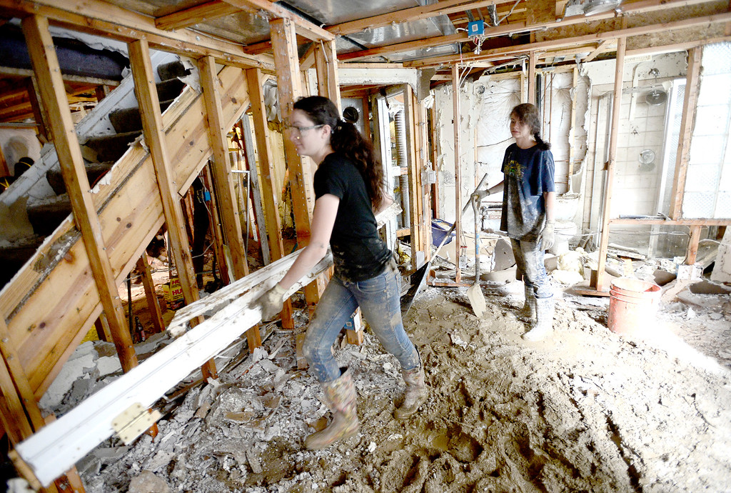 . Kennedy Walters (left) carries wood out of her basement while her cousin Dakota Walters (right) takes short brake after heavy rains caused flooding in Boulder, Colorado September 14, 2013. BOULDER DAILY CAMERA/ Mark Leffingwell