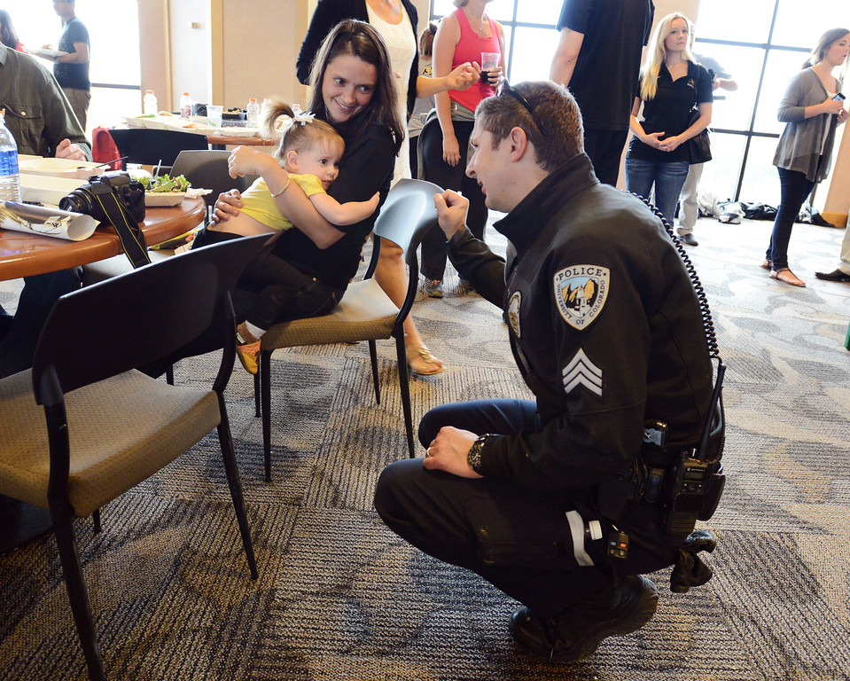 . CU  Police Sergeant Adam Trojanowski, right, chats with Amia Hensberry, 21 months old, in the arms of her mother Karina on Saturday. Cu Athletes served a meal to residents of CU�s Family Housing in the Club Room at Folsom Stadium.   September 14, 2013 staff photo/ David R. Jennings