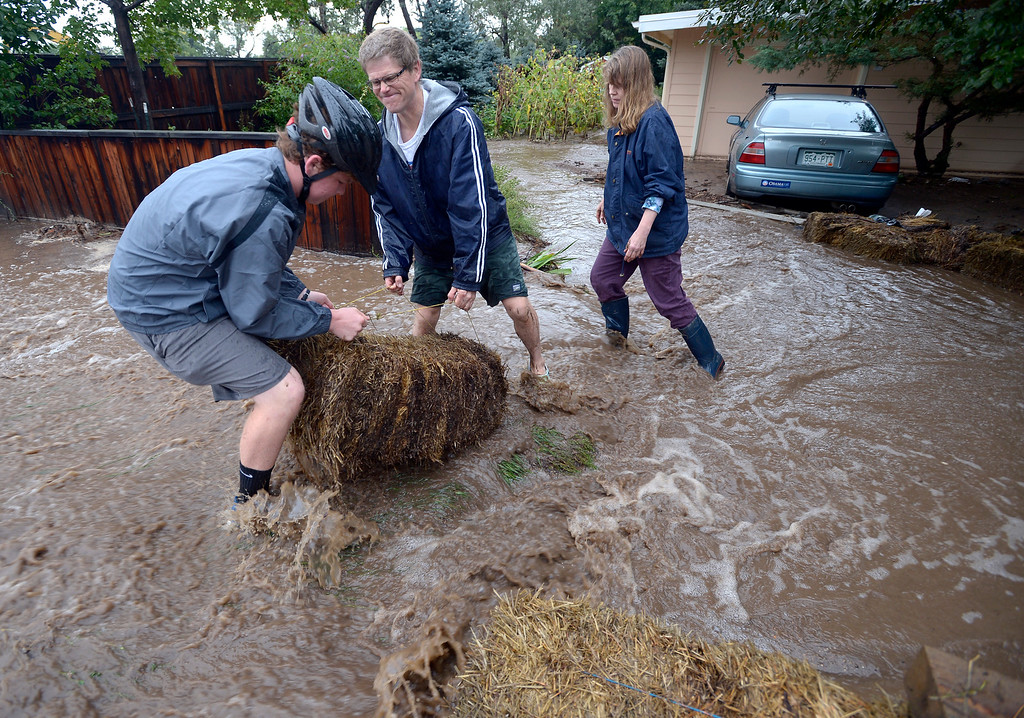 . Kent Shorrock and his wife Astrid Paustian with the help of Patrick Sherman uses straw bales to keep water from their  home in North Boulder of Violet Avenue Friday morning.. Photo by Paul Aiken