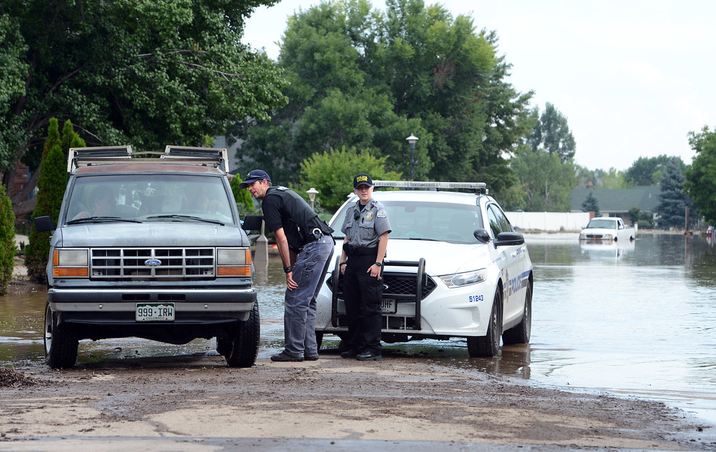 . Longmont Police officers check in with a motorist along Wade Rd, off 9th Street, east of Airport Rd in Longmont, Colorado on September 14, 2013. Cliff Grassmick / September 14, 2013