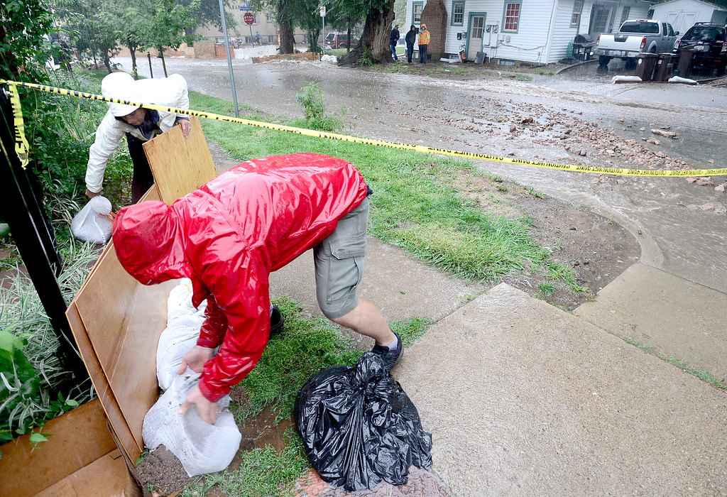 . Jud and Amy Skafe build a small shield to help a neighbor as the water rises on 7th Street from heavy rains in Boulder, Colorado September 12, 2013. BOULDER DAILY CAMERA/ Mark Leffingwell