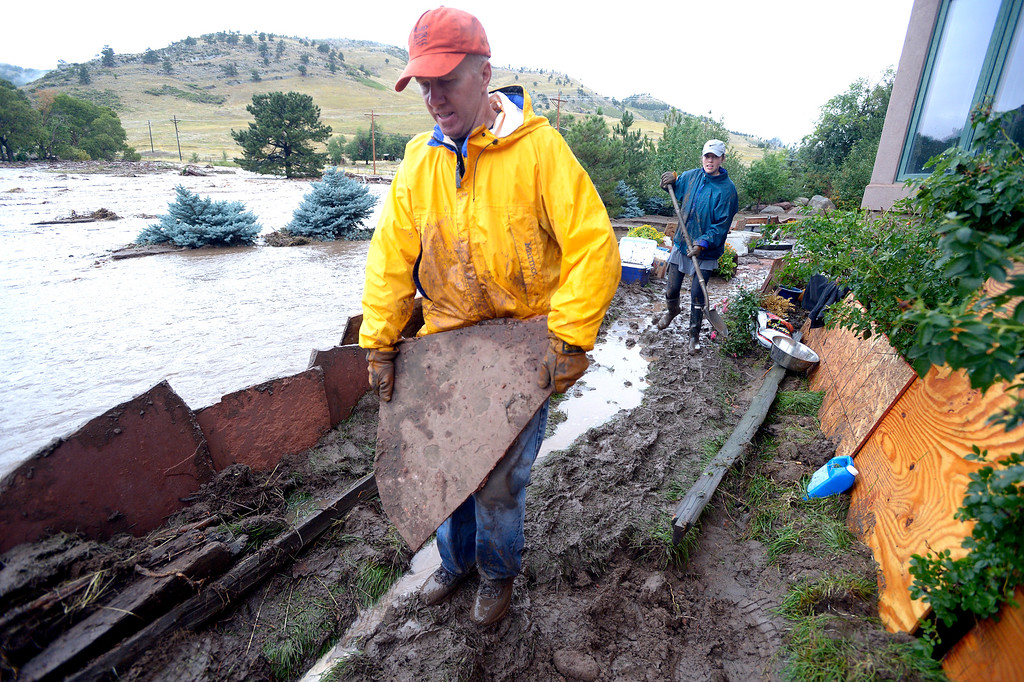 . Steve Stanzel uses patio stones to hold back the water from  a friend  home off Lee Hill Drive in Boulder on Friday.  Photo by Paul Aiken