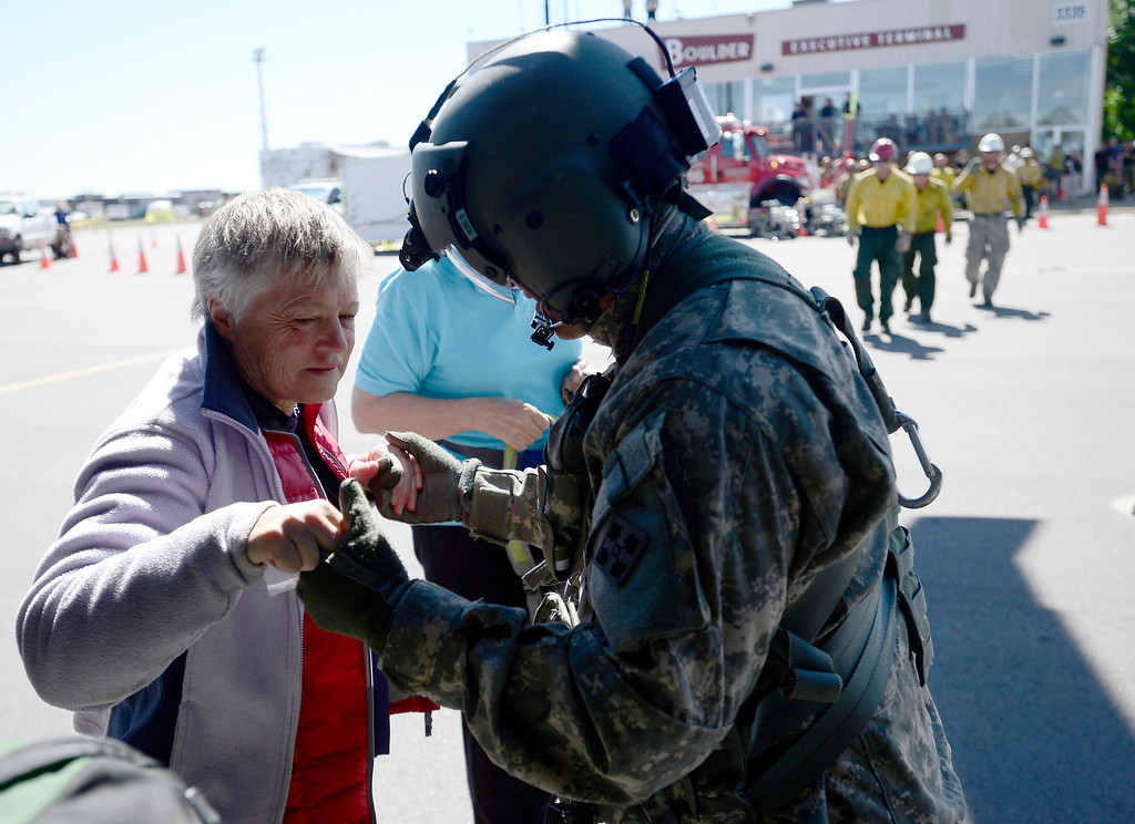 . SFC Keith Bart (R) helps a woman who was winched up to a helicopter flown by members of 2-4 GSAB 4th Infantry Division based in Ft. Carson in near Jamestown, Colorado September 17, 2013. BOULDER DAILY CAMERA/ Mark Leffingwell