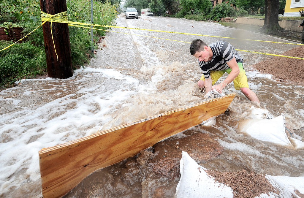. Jake Bennett drops a sand bag down to help funnel water down 7th Street at University as heavy rains cause severe flooding in Boulder, Colorado September 12, 2013. BOULDER DAILY CAMERA/ Mark Leffingwell