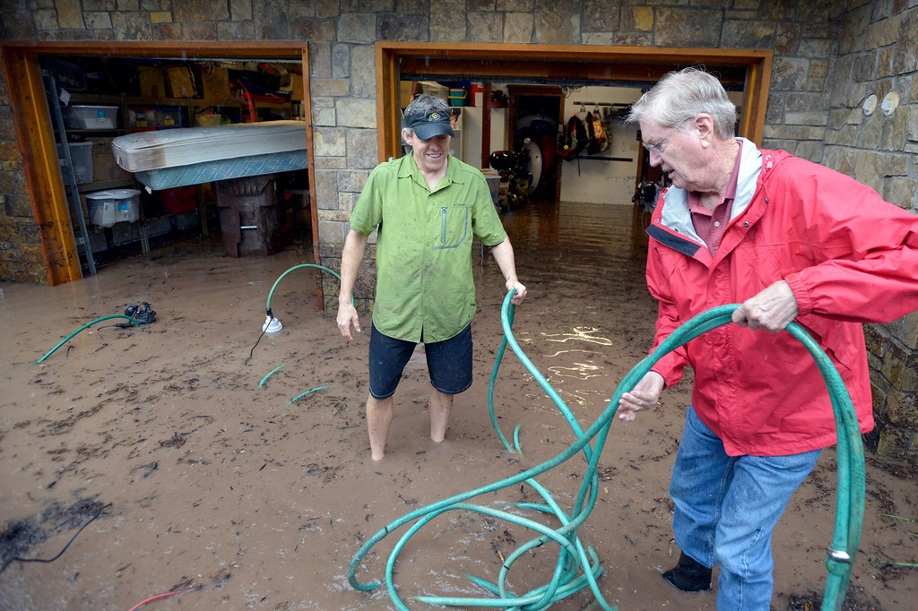 . Charles Drummond, at right, helps his son Chris Drummond set up water pumps to pump out the flooded basement during the heavy flooding on Thursday in Boulder. For a video of the flooding go to www.dailycamera.com  Jeremy Papasso/ Camera