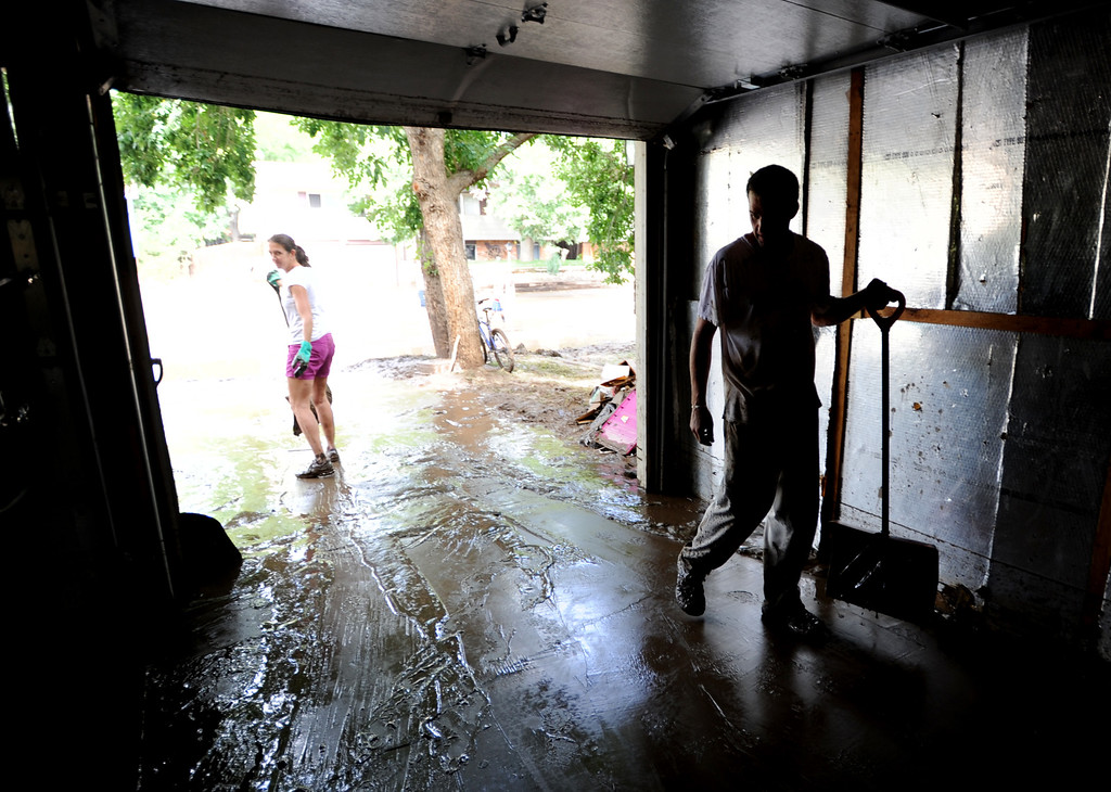 . Stefani Anderson, left, and Mark Swanson clean mud out of the garage of their home on Lefthand Drive in Longmont, Colorado on September 14, 2013. Cliff Grassmick / September 14, 2013