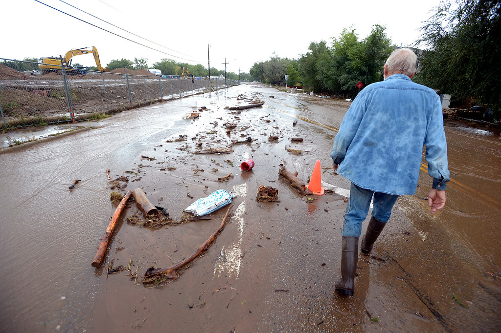 . Win Franklin walks through debris on Violet Avenue on Friday September 13, 2013 ....Photo by Paul Aiken / The Daily Camera