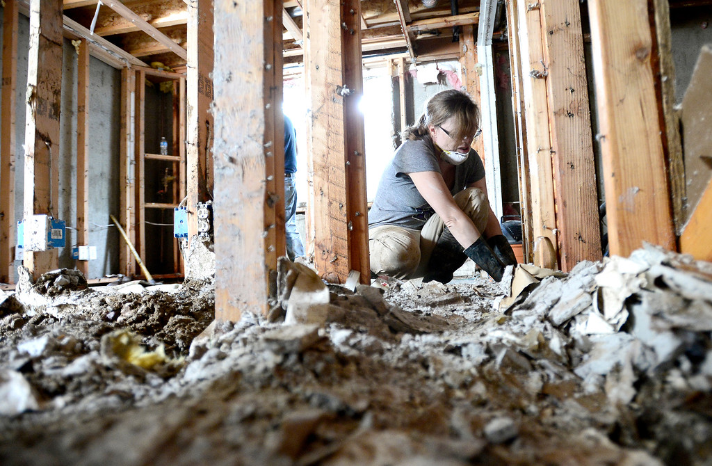 . Terri Walters works to pull base boards and sheet rock from the studs in her basement after heavy rains cause flooding to reach 8-feet-deep in her home on Qualla Drive in Boulder, Colorado September 14, 2013. BOULDER DAILY CAMERA/ Mark Leffingwell