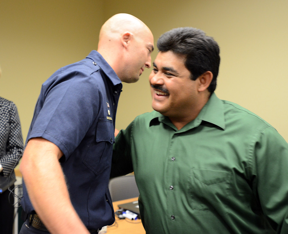 . North Metro Fire Rescue engineer John Cook, left, gives Roy Ortiz a hug after a news conference at Good Samaritan Hospital on Friday. Ortiz was rescued by Cook after being trapped in the water of Rock Creek at Dillon Road on Thursday.  September 6, 2013 staff photo/ David R. Jennings
