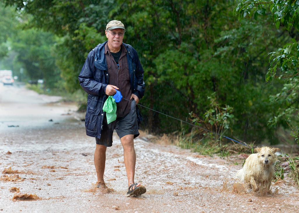 . John Gerstle and his dog Gizmo walk up the flooded Linden Street during the heavy flooding on Thursday in Boulder. For a video of the flooding go to www.dailycamera.com  Jeremy Papasso/ Camera