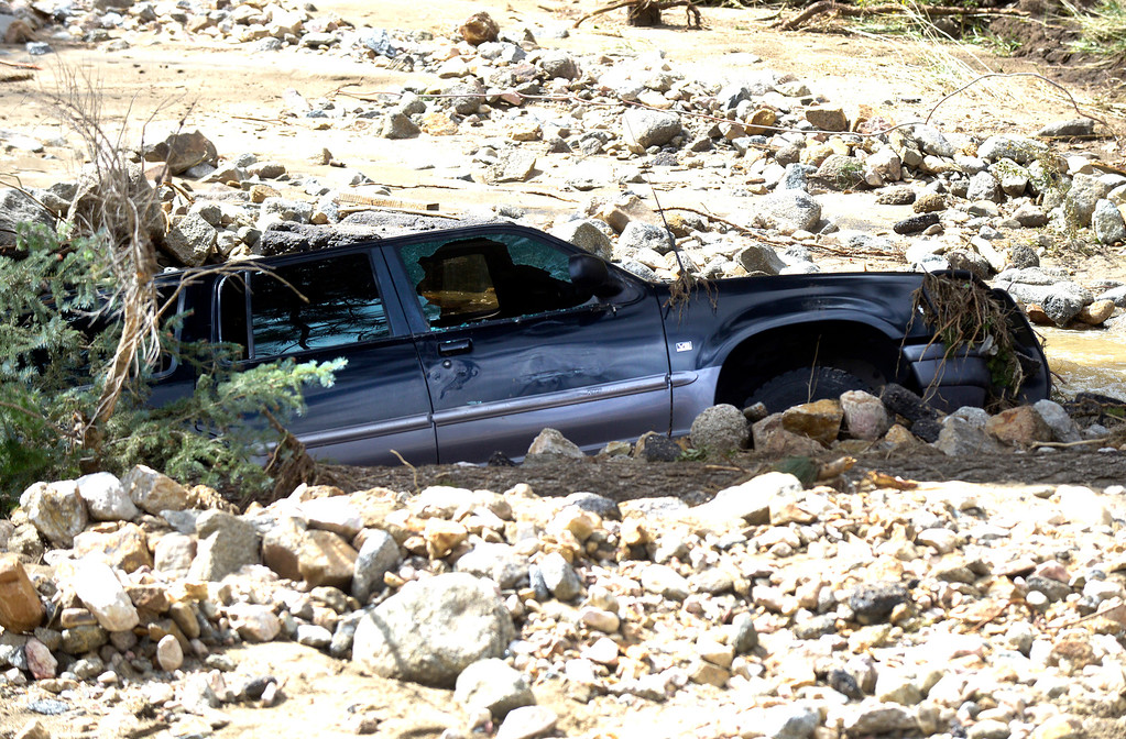 . A vehicle is submerged in mud and water following the flood on Tuesday, Sept. 17, in the Fourmile Canyon area of Boulder County.  Jeremy Papasso/ Camera