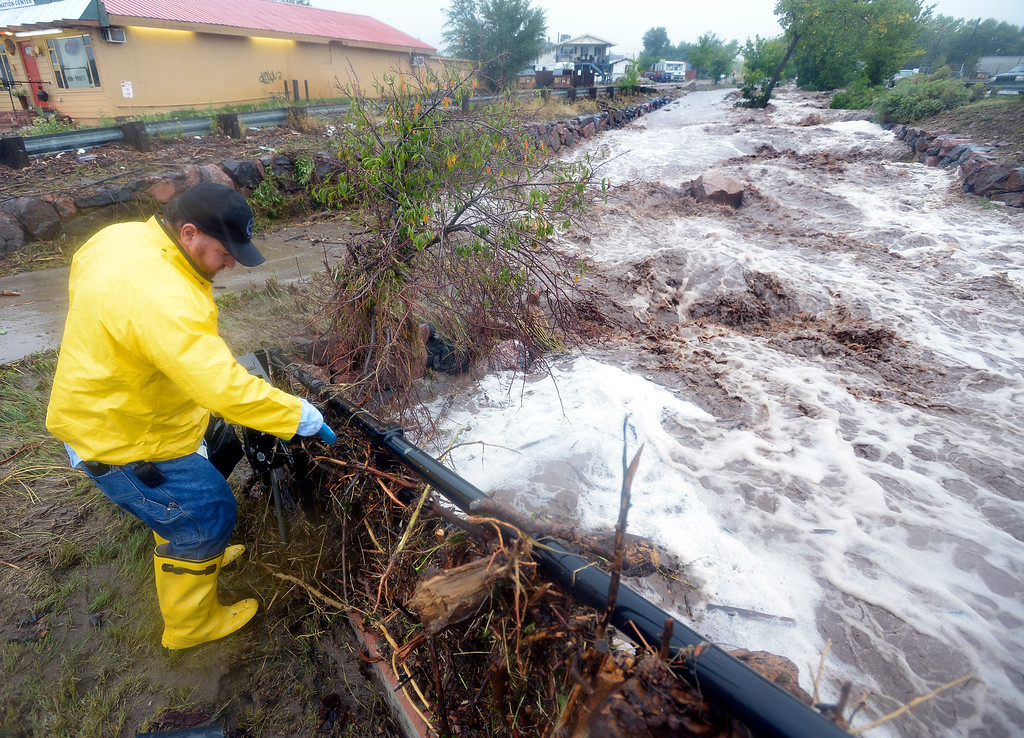 . Trent Fallica of the City of Boulder Traffic Signal Department checks on an electrical box next to a raging creek during the  flood in north Boulder Thursday morning.  Photo by Paul Aiken / www.dailycamera.com