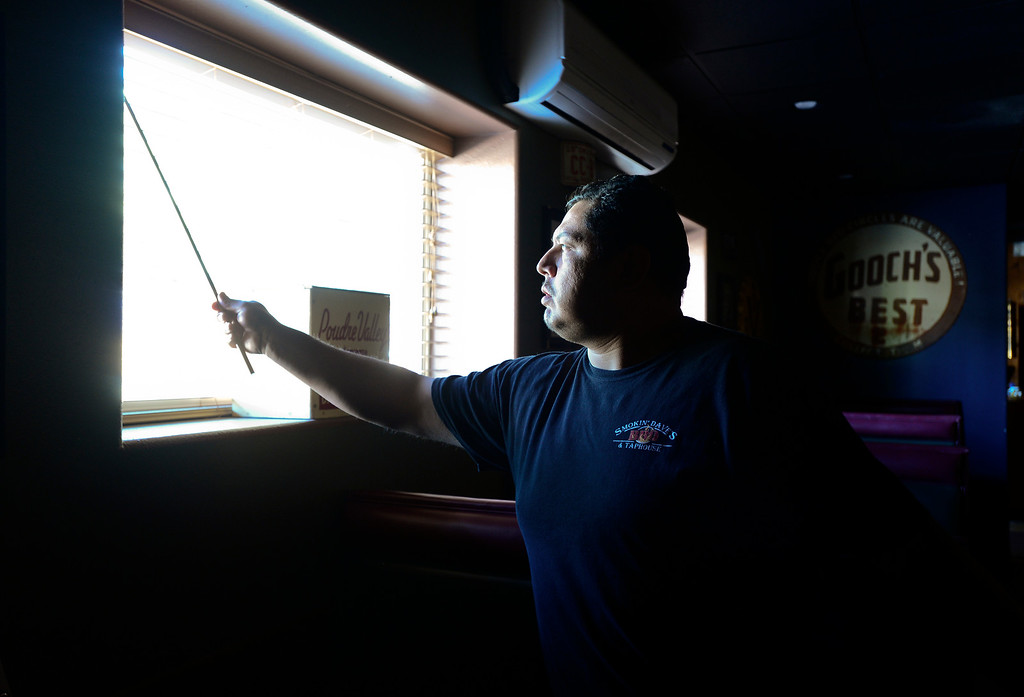 . Smokin\' Daves BBQ and Taphouse Manager Louis Montes opens blinds to let light into the building while checking for damage, Wednesday, Sept. 18, 2013, in Lyons. All the utilities for the town of Lyons are currently down including, water, power and sewer service. (Matthew Jonas/Times-Call)