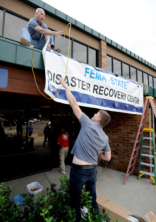 . Francis Duffy, top, and Sam Veucasovic, put up the signs for the recovery center. The City of Boulder and Boulder County are opened a joint Disaster Assistance Center at 1 p.m. on Thursday, Sept. 19, at 5495 Arapahoe Ave. in Boulder. This center, along with the Disaster Assistance Center in Longmont, is available all to Boulder County residents impacted by the flood.For more flooding videos and photos, www.dailycamera.com. Cliff Grassmick  / September 19, 2013
