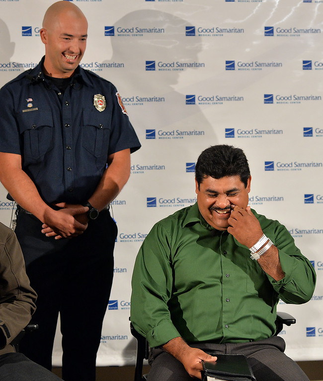 . Roy Ortiz, right, laughs with North Metro Fire Rescue engineer John Cook after they explained the swift water rescue after Ortiz car crashed into the water at Dillon Road, last Thursday, during a news conference at Good Samaritan Hospital on Friday.   September 13, 2013 staff photo/ David R. Jennings
