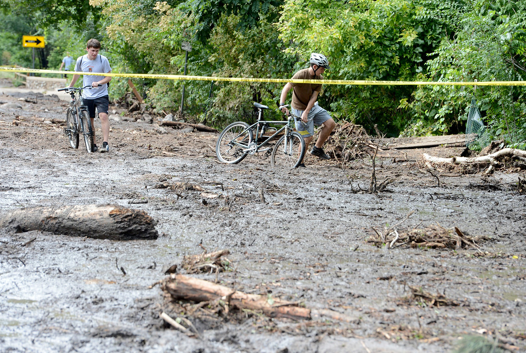 . Two cyclists walk through the mud on west Arapahoe Ave. on Friday afternoon. For more flooding videos and photos, www.dailycamera.com. Cliff Grassmick  / September 13, 2013