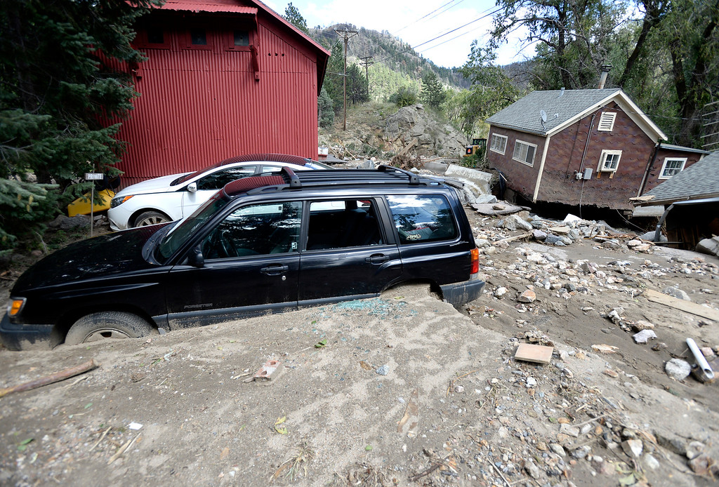 . Cars are seen buried near a destroyed home in Salina on Tuesday, Sept. 17, in the Fourmile Canyon area of Boulder County. For more photos and video of the flood rescue go to www.dailycamera.com Jeremy Papasso/ Camera