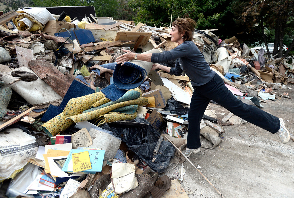 . Trudy Nickola, of Boulder, throws a flood damaged piece of carpet into a massive pile of flood damaged property at the North Boulder Park on Wednesday, Sept. 18, in Boulder. For more photos and video of the flood go to www.dailycamera.com Jeremy Papasso/ Camera