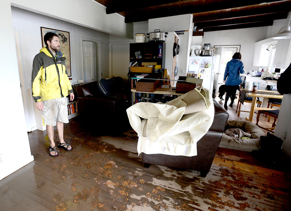 . Levin Sliker (left) and Elizabeth Aisenbrey (right) look over the water damage in their home after heavy rains caused floodingin Boulder, Colorado September 13, 2013. BOULDER DAILY CAMERA/ Mark Leffingwell