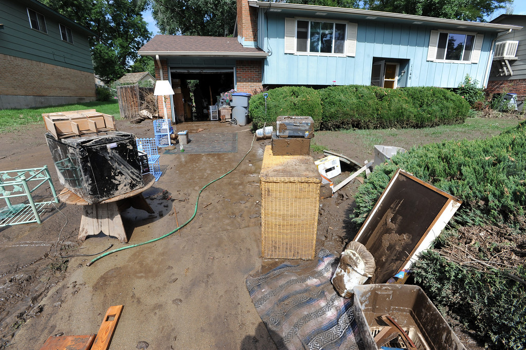 . The flood damaged belongings of this family are taken outside of this mud filled home on Lefthand Drive in Longmont, Colorado on September 14, 2013. Cliff Grassmick / September 14, 2013