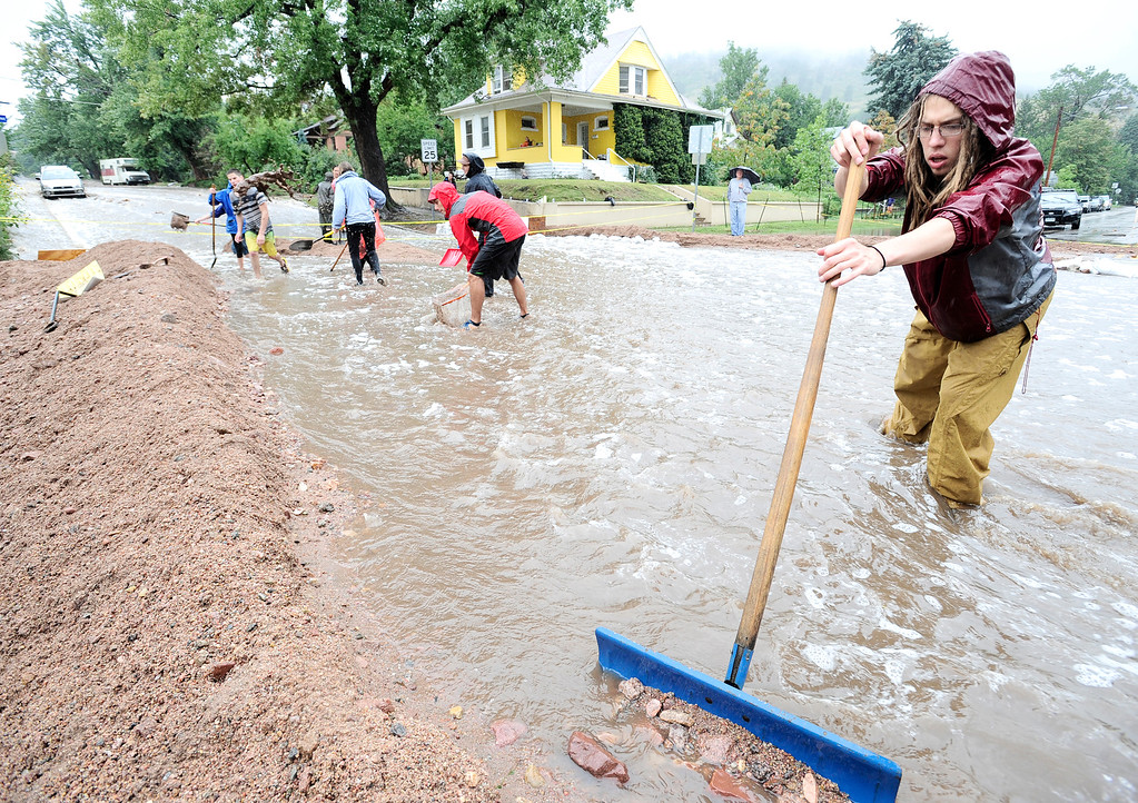 . Nick Carter joins his neighbors shoveling wash out debris into a dyke to funnel water down 7th Street at University as heavy rains cause severe flooding in Boulder, Colorado September 12, 2013. BOULDER DAILY CAMERA/ Mark Leffingwell