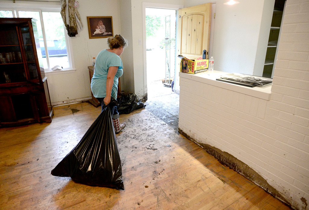 . Mary Bogetveit drags a bag of water soaked books after water filled her home on Gapter Road from heavy rains causing flooding in Boulder, Colorado September 14, 2013. BOULDER DAILY CAMERA/ Mark Leffingwell