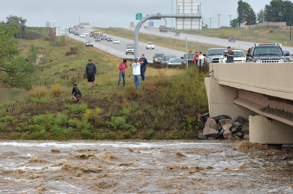 . People stop on the bridge over south bound I-25 to look at the flood waters of the St. Vrain River on Friday.   September 13, 2013 staff photo/ David R. Jennings