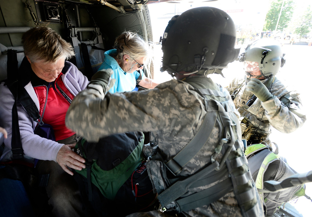 . Staff Sgt. Jose Pantoja helps unbuckle two women rescued outside Jamestown Colorado as they land at Boulder Municipal Airport in Boulder Colorado on Tuesday. Jamestown was hard hit by flood waters. The helicopter was flown by members of 2-4 GSAB 4th Infantry Division based in Ft. Carson, Colorado September 17, 2013. BOULDER DAILY CAMERA/ Mark Leffingwell