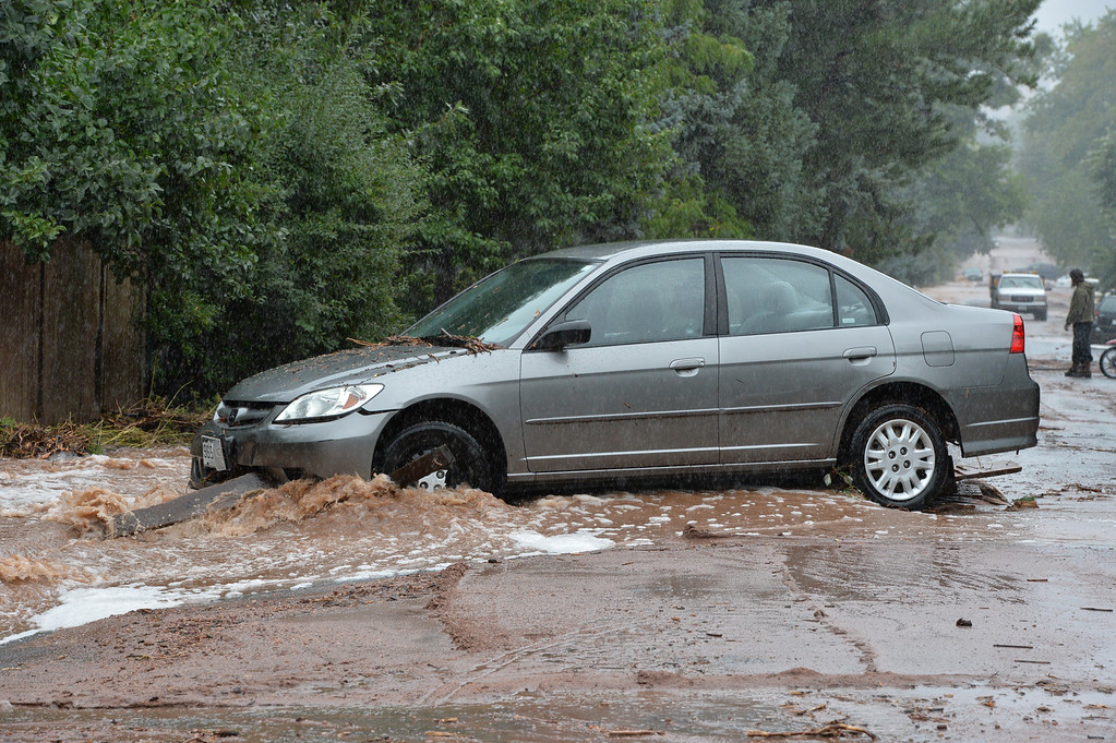 . A car is hit by water and debris in the flooding along Mariposa Ave. and 20th St.  in Boulder on Thursday. September 12, 2013 staff photo/ David R. Jennings