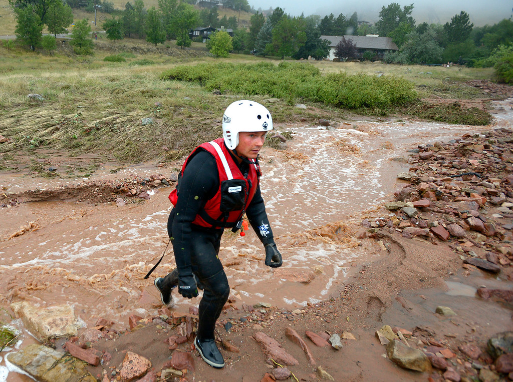 . Brighton Fire Rescue firefighter Brian Guyer searches for a possible drowning victim on Linden Street during the heavy flooding on Thursday in Boulder. For a video of the flooding go to www.dailycamera.com  Jeremy Papasso/ Camera