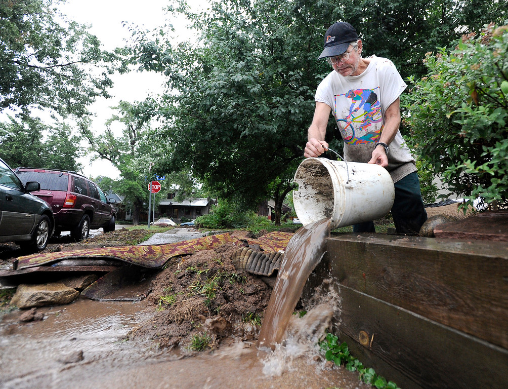 . Jeff Busch uses a bucket to scoop water from his home near University Avenue on Thursday, Sept. 12, in Boulder. For more photos and video of the flood go to www.dailycamera.com Jeremy Papasso/ Camera