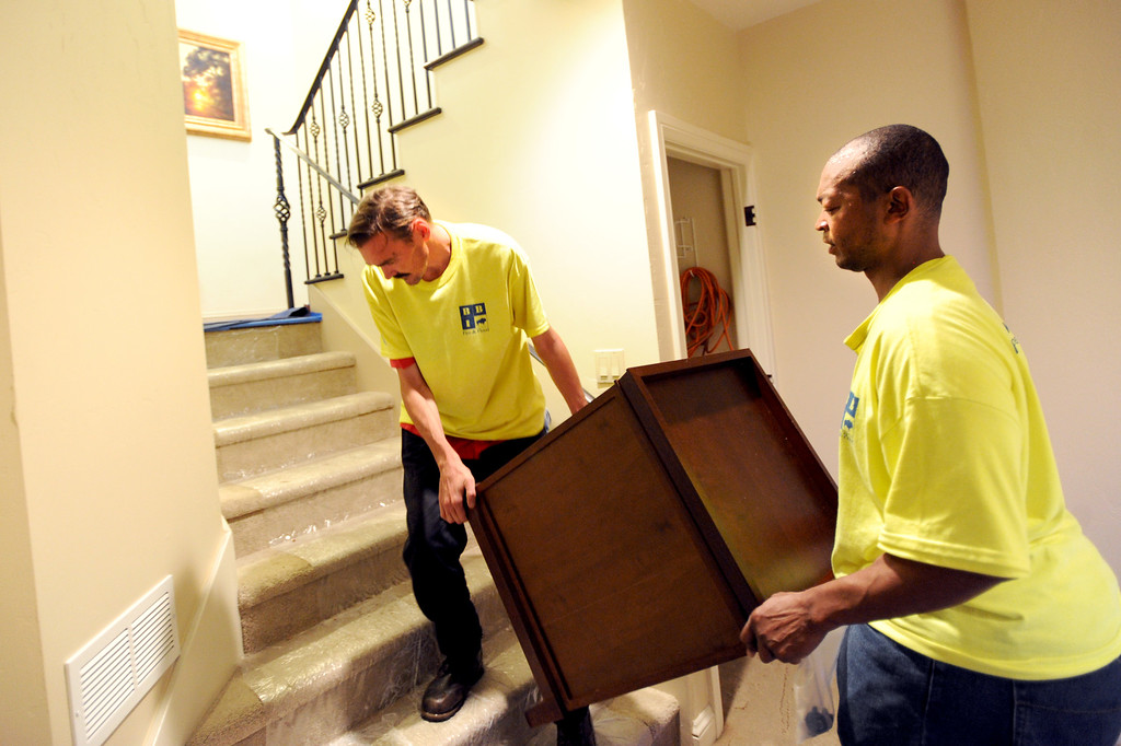 . Juston Travis, left, and Ken Daugherty both of Buffalo Builders Inc, flood and fire catastrophe team, move out damaged furniture at a Boulder home near North Boulder Park. For more flooding videos and photos, www.dailycamera.com. Cliff Grassmick  / September 18, 2013