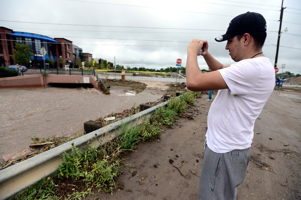 . Javier Ariano takes photos of a raging Four Mile Creek in Boulder, Colorado on Sunday September 15, 2013.  Rain fell heavily again today increasing fears of more flooding in the community. Photo by Paul Aiken / The Daily Camera / Saturday September 15, 2013