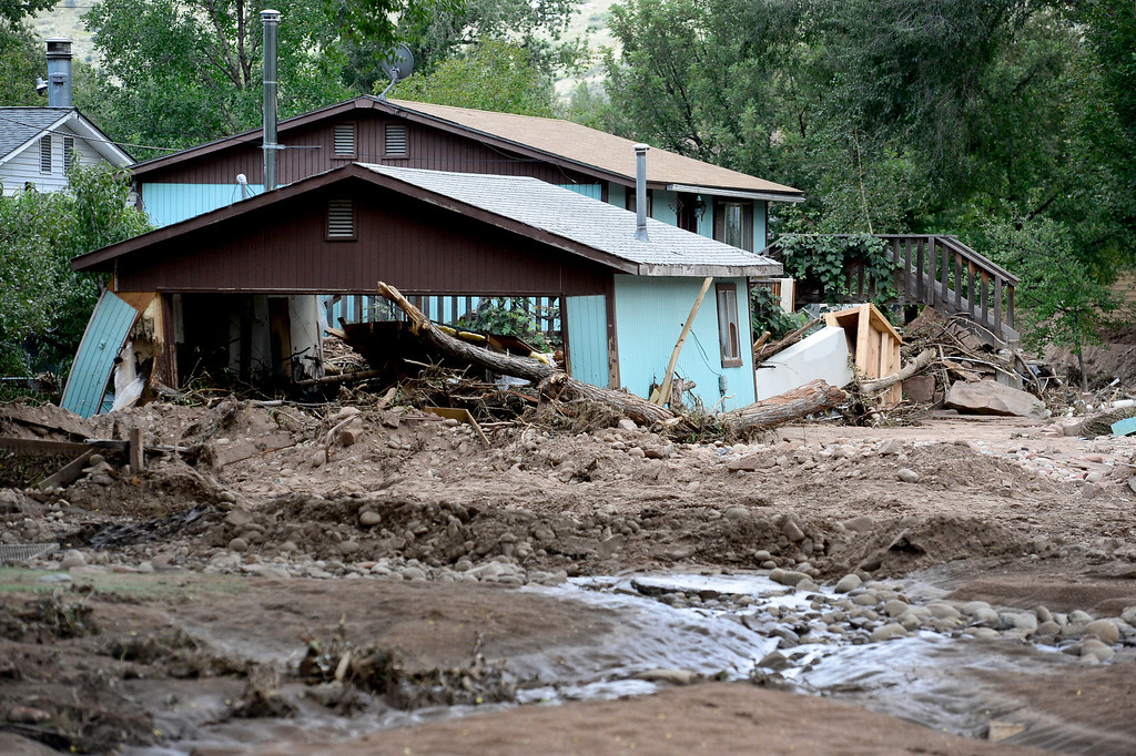 . Streets filled with mud and debris and a garage that appears to be leaning is seen, Wednesday, Sept. 18, 2013, in Lyons. (Matthew Jonas/Times-Call)