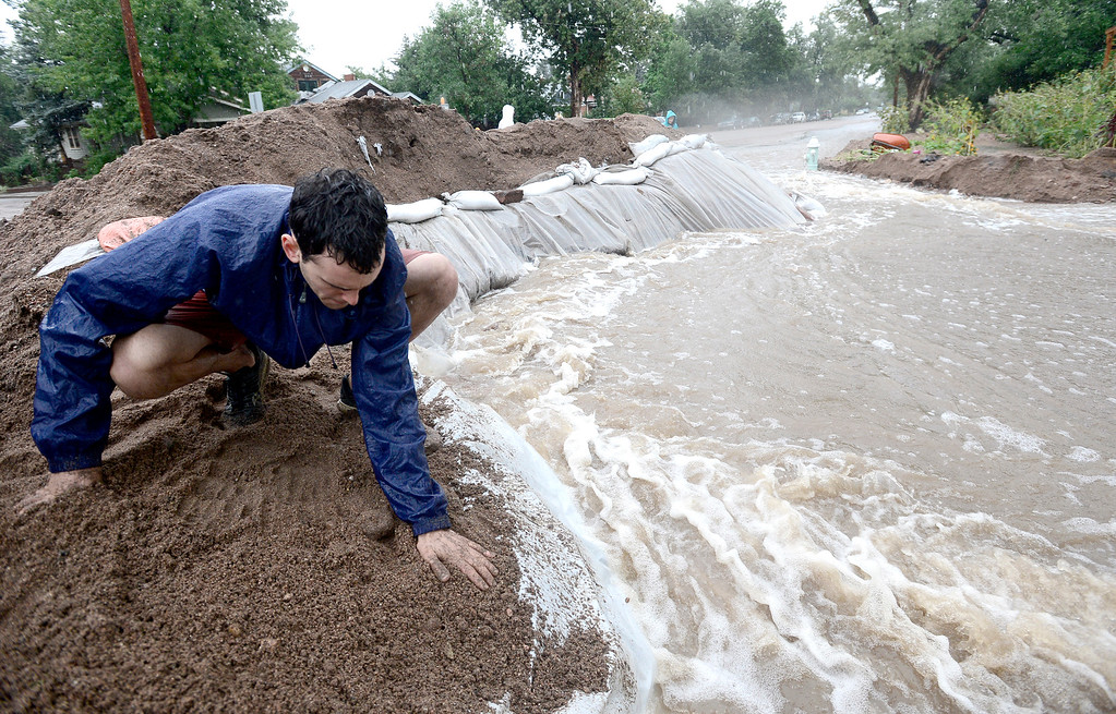 . Erez Shani packs down soil at the top of a berm that is redirecting water as heavy rains cause flooding to rise in Boulder, Colorado September 15, 2013. BOULDER DAILY CAMERA/ Mark Leffingwell