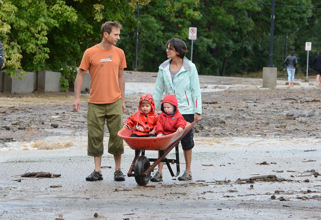 . Steven Phillips, left, his wife, Tila Duhaime, and his son, Wiley Phillips, left in the wheelbarrow, with his friend, Avery McCluney, walk near a flooding Boulder Creek on September 13, 2013 in Boulder, Colorado. For more flooding videos and photos, www.dailycamera.com. Cliff Grassmick  / September 13, 2013