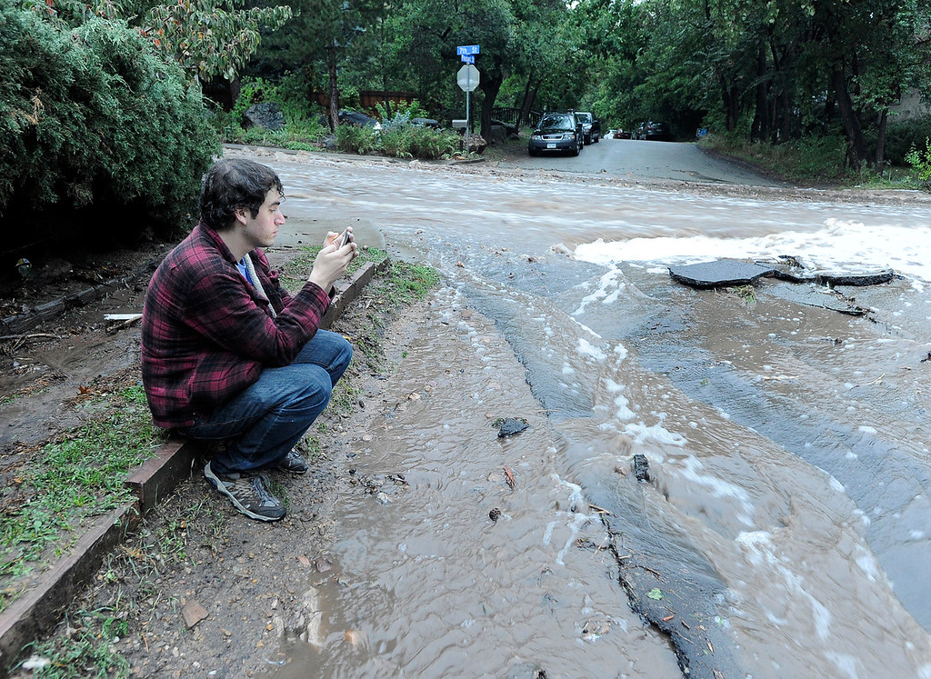 . Zach Green, of Boulder, looks at his cell phone while sitting next to the flooding waters at the intersection of 7th and Pleasant Streets on Thursday, Sept. 12, in Boulder. For more photos and video of the flood go to www.dailycamera.com Jeremy Papasso/ Camera