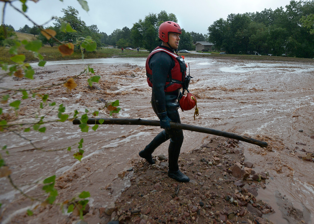 . Brighton Fire Rescue firefighter Clint Mader searches for a possible drowning victim during the heavy flooding on Thursday in Boulder. For a video of the flooding go to www.dailycamera.com  Jeremy Papasso/ Camera