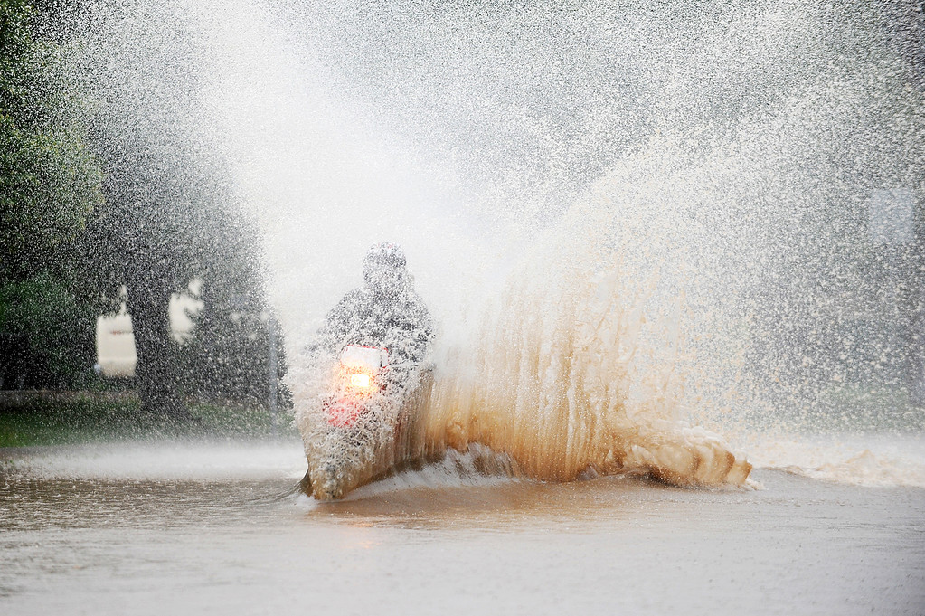 . An unidentified man rides his dirt bike through flood waters at the corner of Balsam and 9th Street in Boulder on Thursday, September 12, 2013. (Kira Horvath/ Daily Camera)